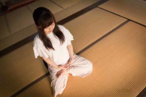 マインドフルネスをする為に畳の上で胡座で座って目をつぶる女性