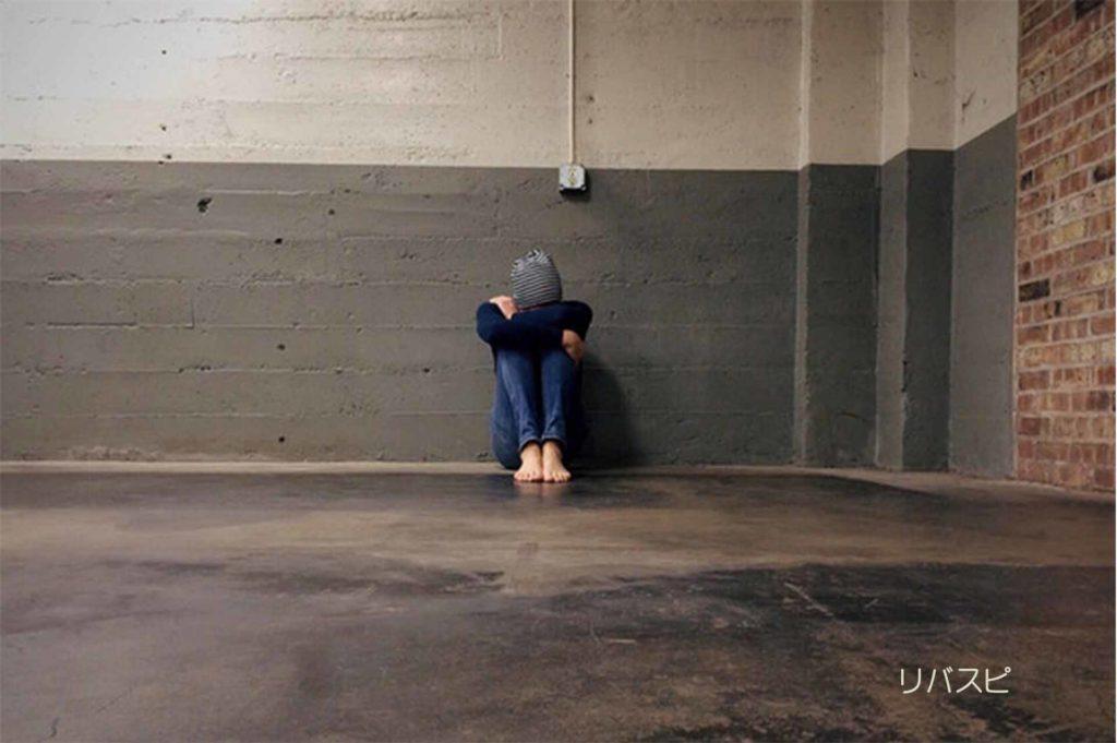 孤独で膝を抱えて頭を下に向けている女性