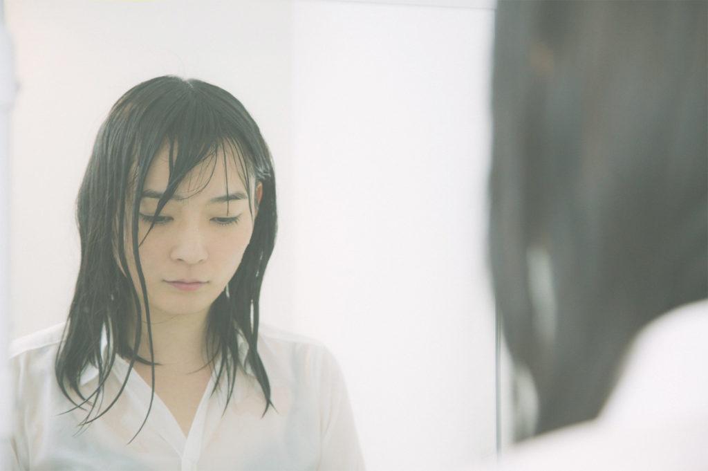 髪が濡れて鏡の前で立ちすくむ女の子