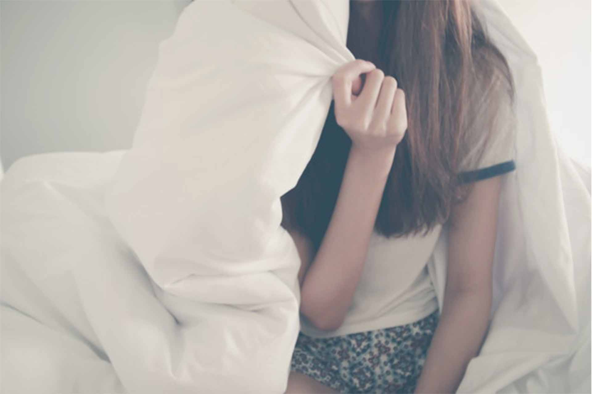 やりたいけどやる気が起きずにベッドの中に入っている女性