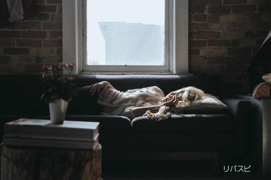 毎日の繰り返しで何もせずにソファーで横になる女性
