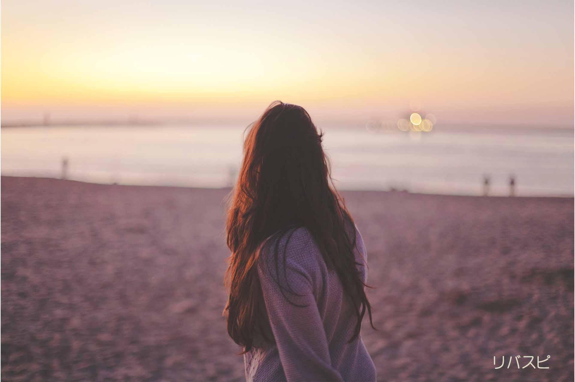 悩みを繰り返して海沿いを歩く女性